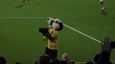 The mascot is a badger in a yellow shirt.