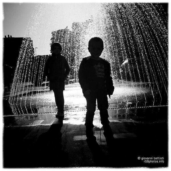 Fotografia controluce di due bambini di fronte ad una fontana cittadina