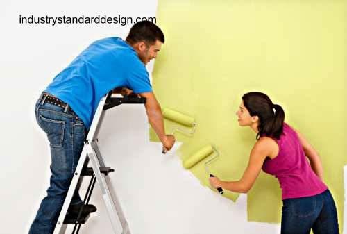 Dos personas dueños de casa pintando una pared