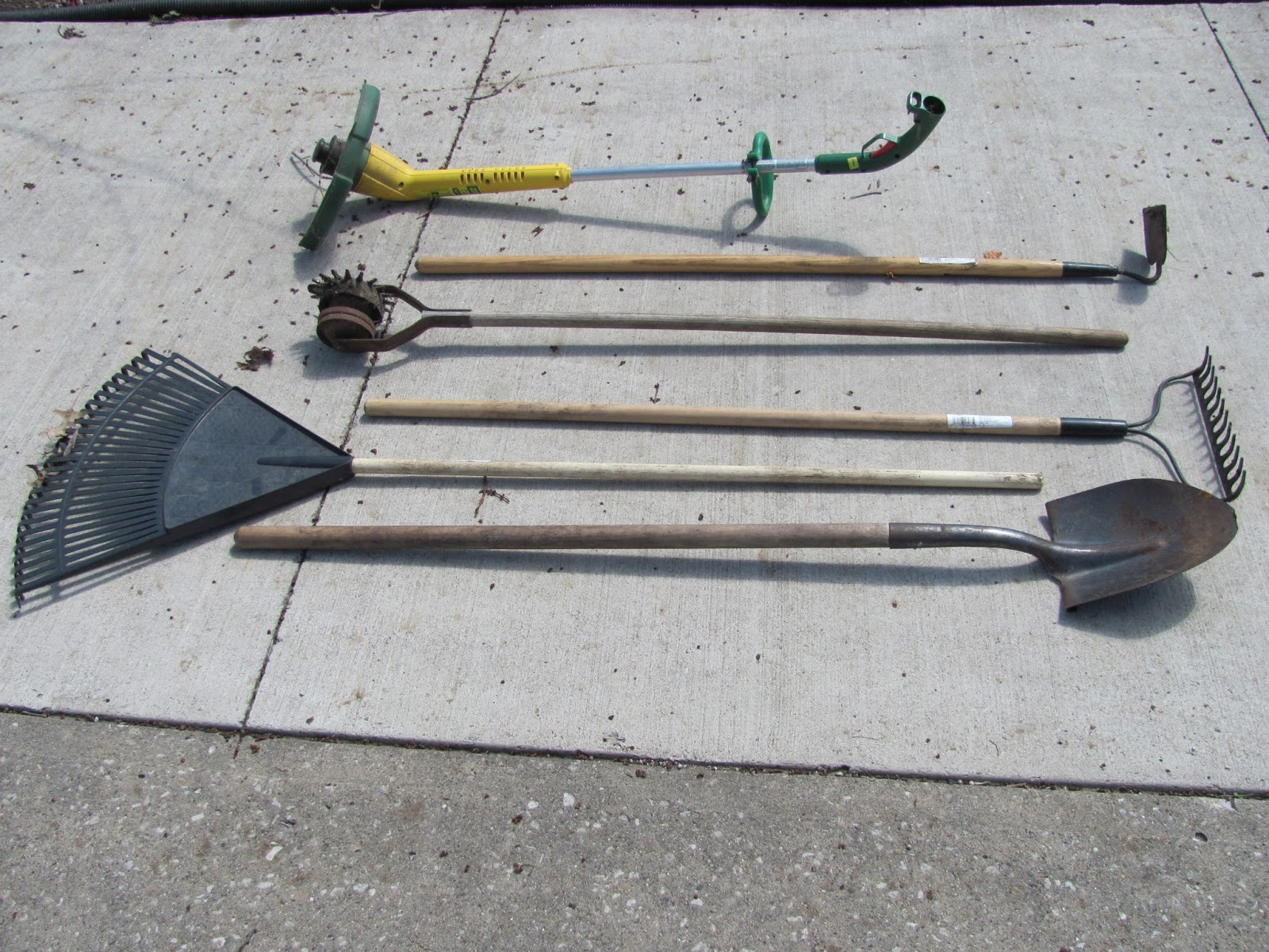 Shovel, leaf rake, garden rake, edger, hoe, and trimmer on display before being sold on Craigslist