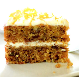 slice from a classic carrot cake with cream cheese filling and frosting and orange zest as a garnish