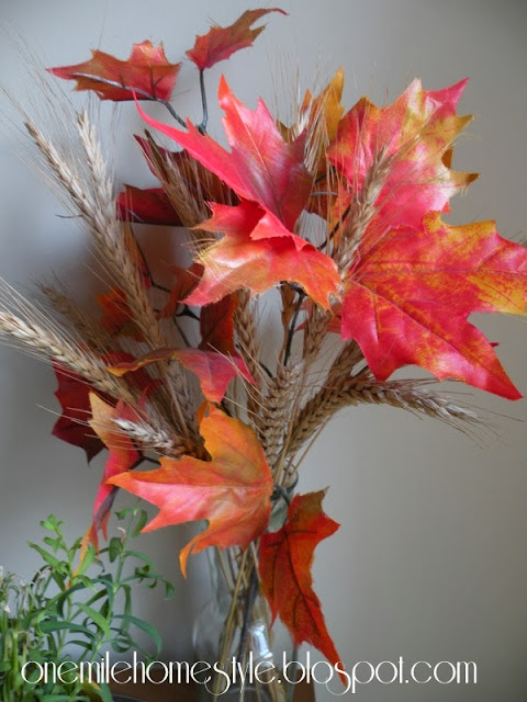 Vase of wheat and fall leaves