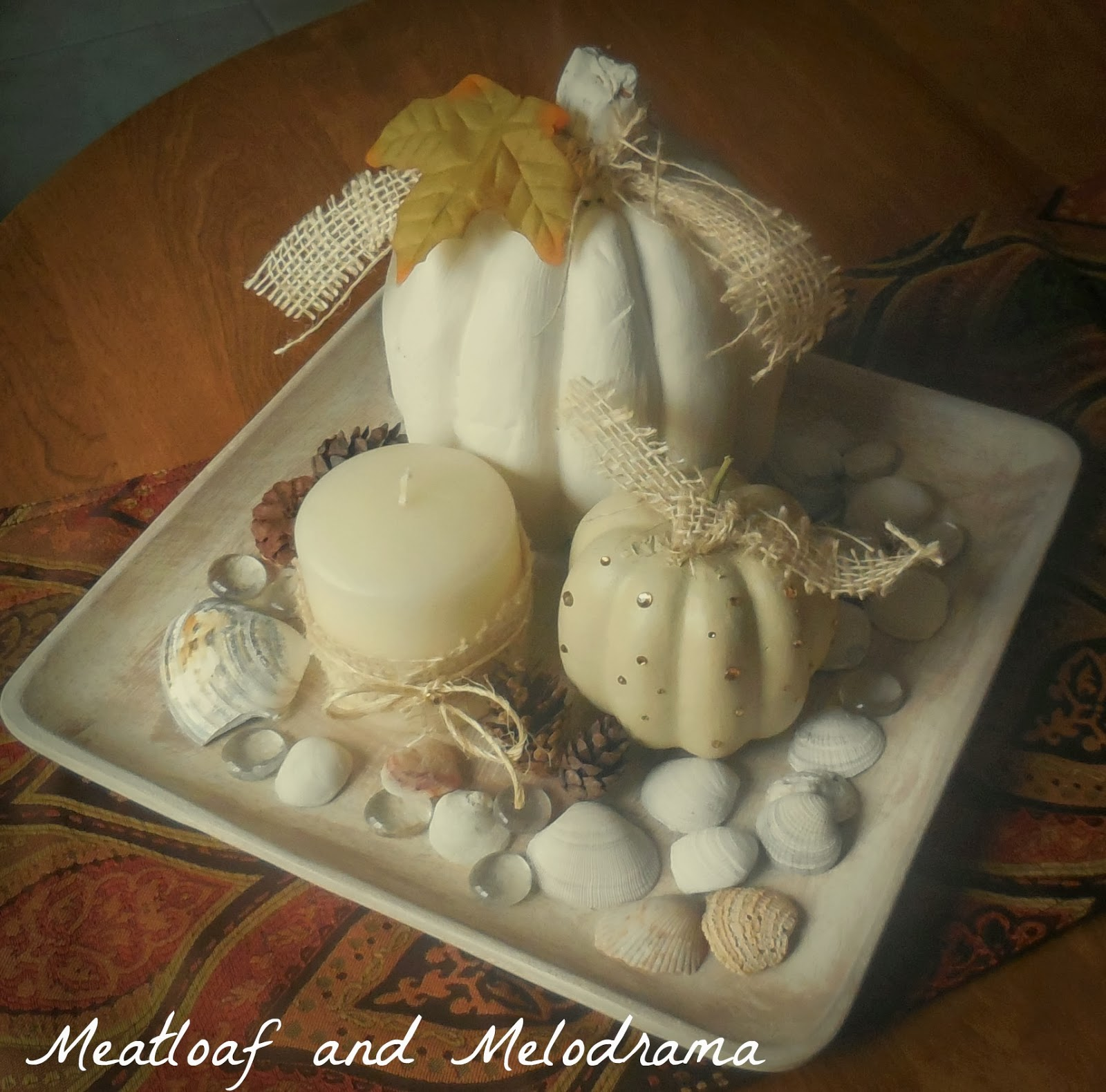 wood tray with white pumpkins candle pine cones and seashells