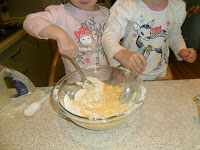 Two children mixing pikelet mixture.