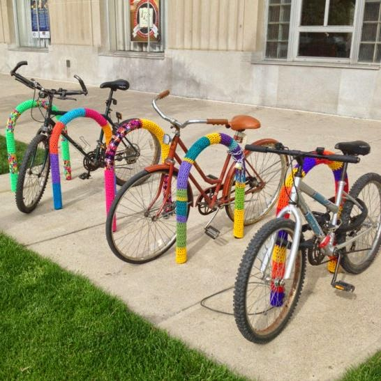 Bicycles parked between upside-down U-shaped bike racks that have been covered with multicolored knitting.