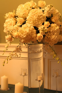 Tall all white classic mounded arrangement with white hydrangea, roses, stock and orchids with hanging crystals