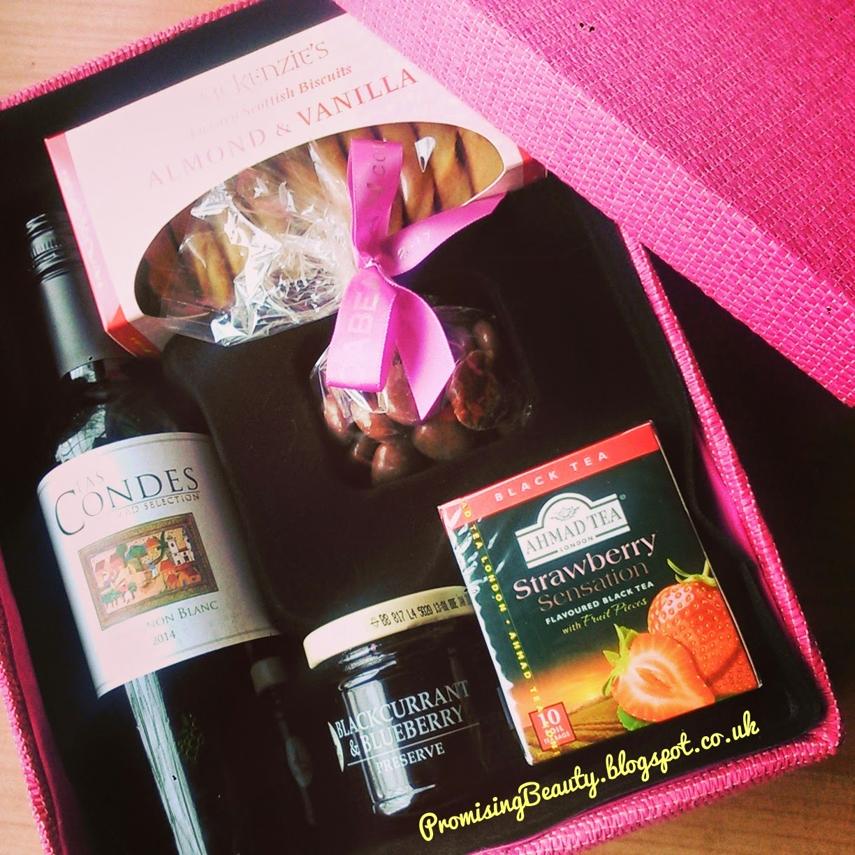 Hamper for her from interflora with strawberry fruit tea, blackcurrant and blueberry jam, almond vanilla biscuits, chocolate caramels and las condes wine.
