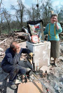 Radenko, left, and Mileka Prtenyakovic, cry in what remains of their home in the city of Chachak