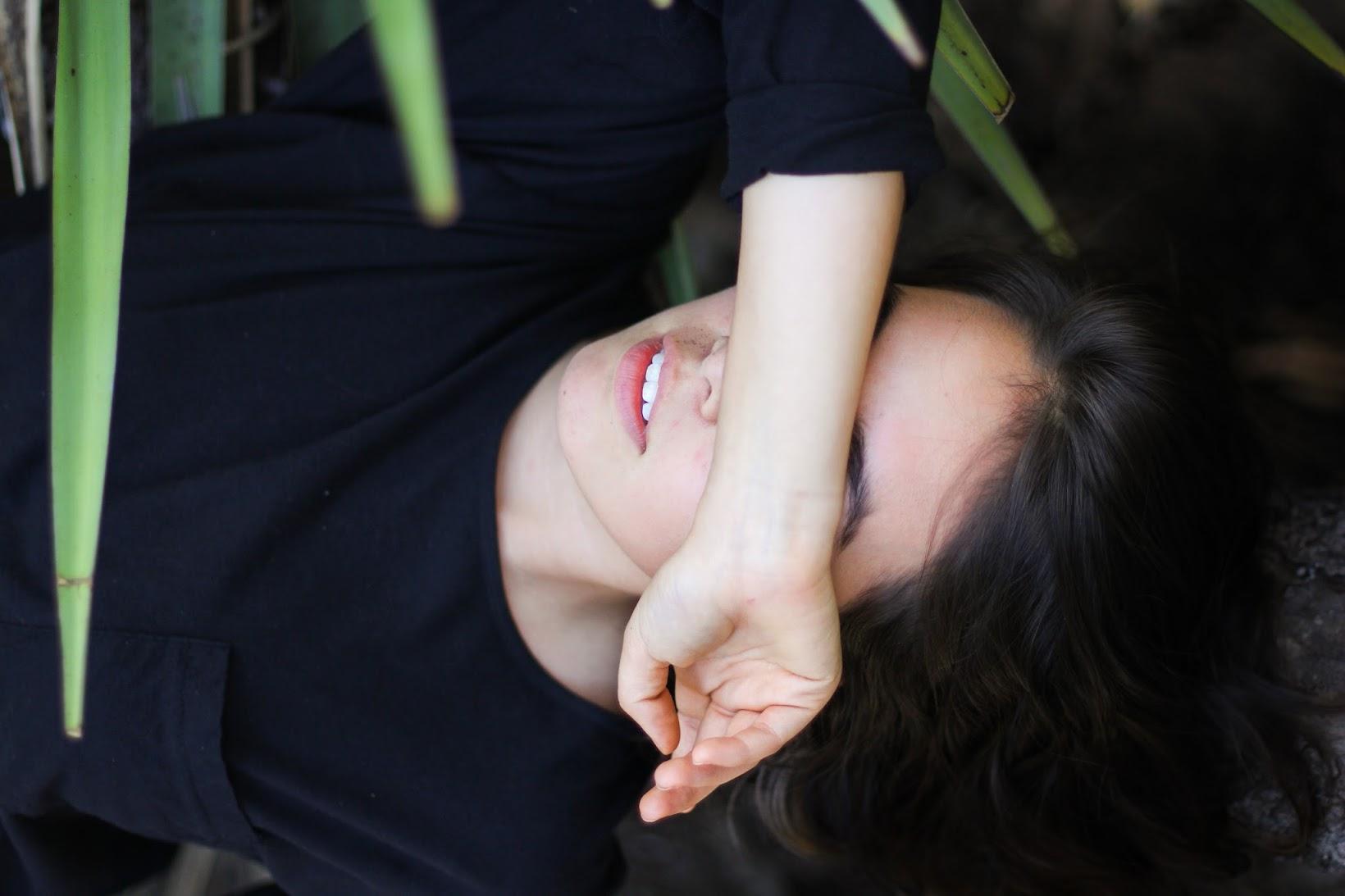 A girl laying down in a cactus garden.