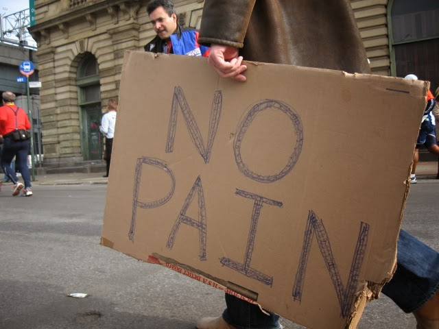 "Photograph of man holding a sign reading ""No Pain"""