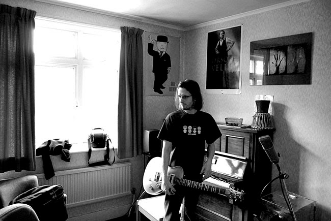 Musician Steven Wilson in black shirt, long hair, holding guitar in front of piano in his English Home Studio