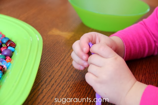 Manipulating beads on pipe cleaners is a great fine motor activity for toddlers