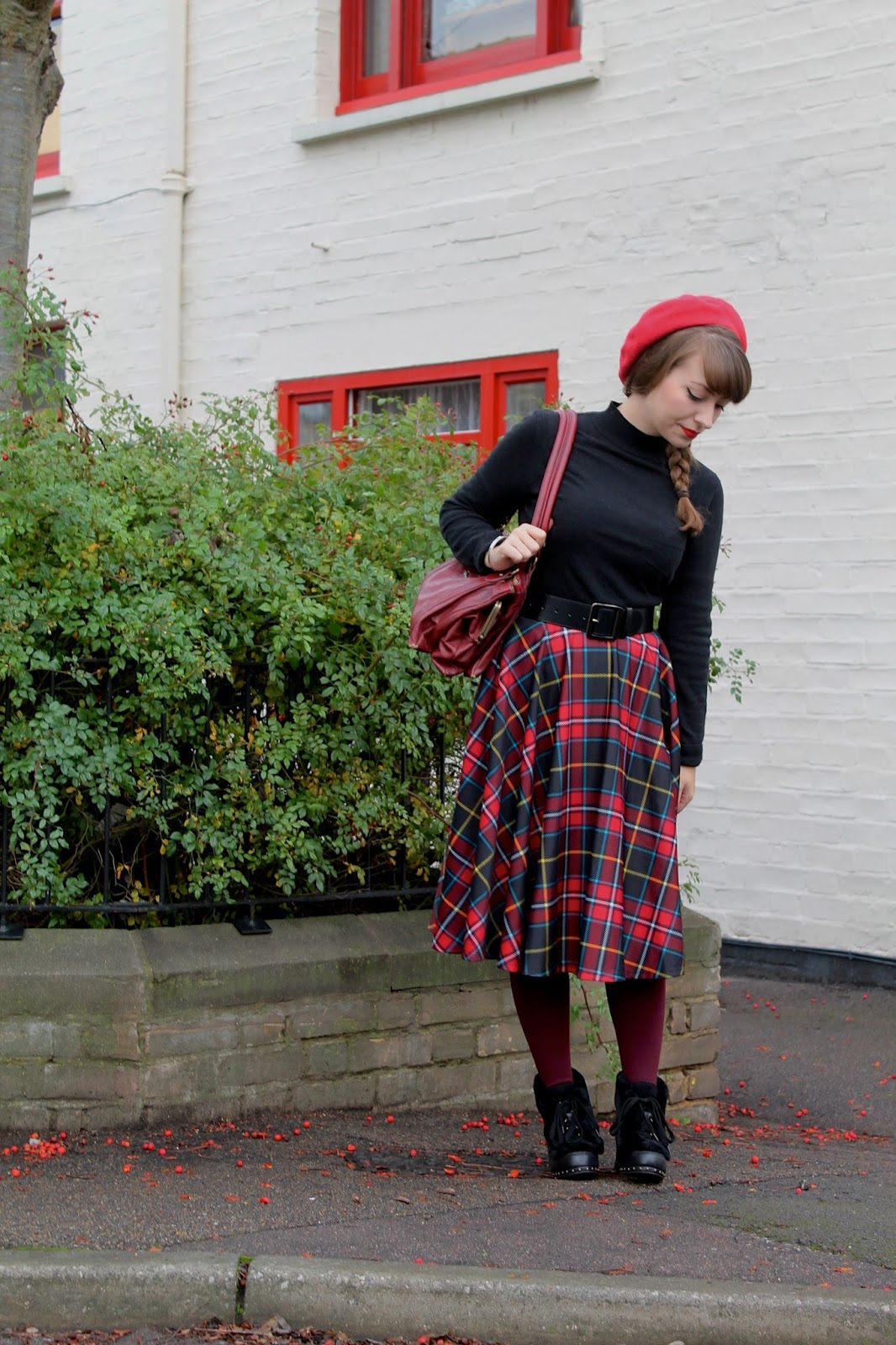 1950s style outfit with plaid full skirt, fur boots and beret