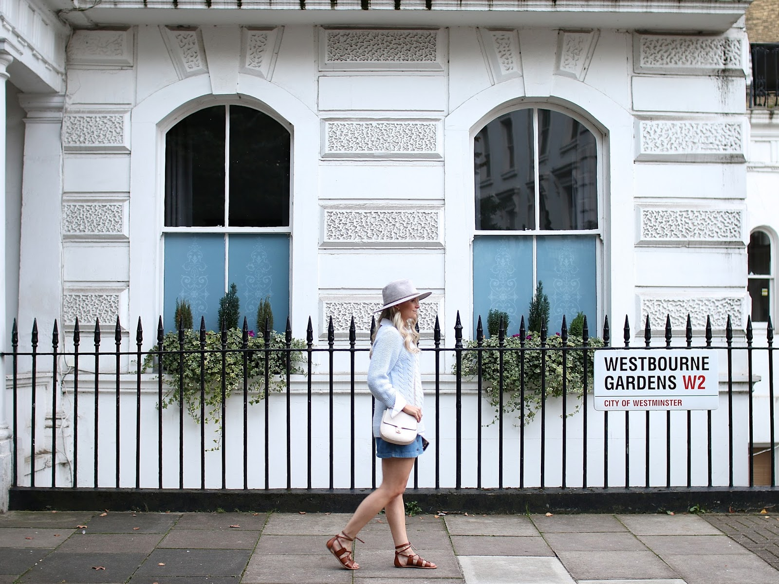a women wandering through hotting hill wearing an all blue outfit and grey hat