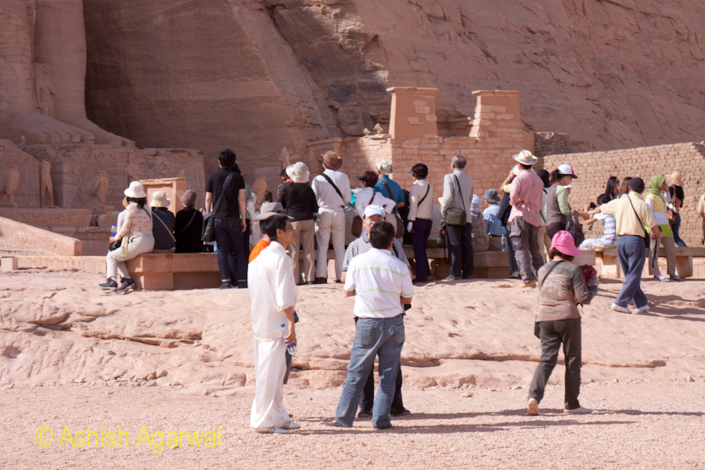 Tourists at the base of the statues at the Abu Simbel temple in Egypt