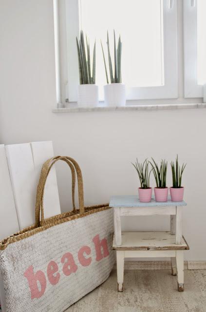 Dekoration vor einem Fenster mit zwei übereinander gestapelten Hockern und drei Bogenhanfpflanzen darauf daneben eine Strandtasche mit Schriftzug Beach