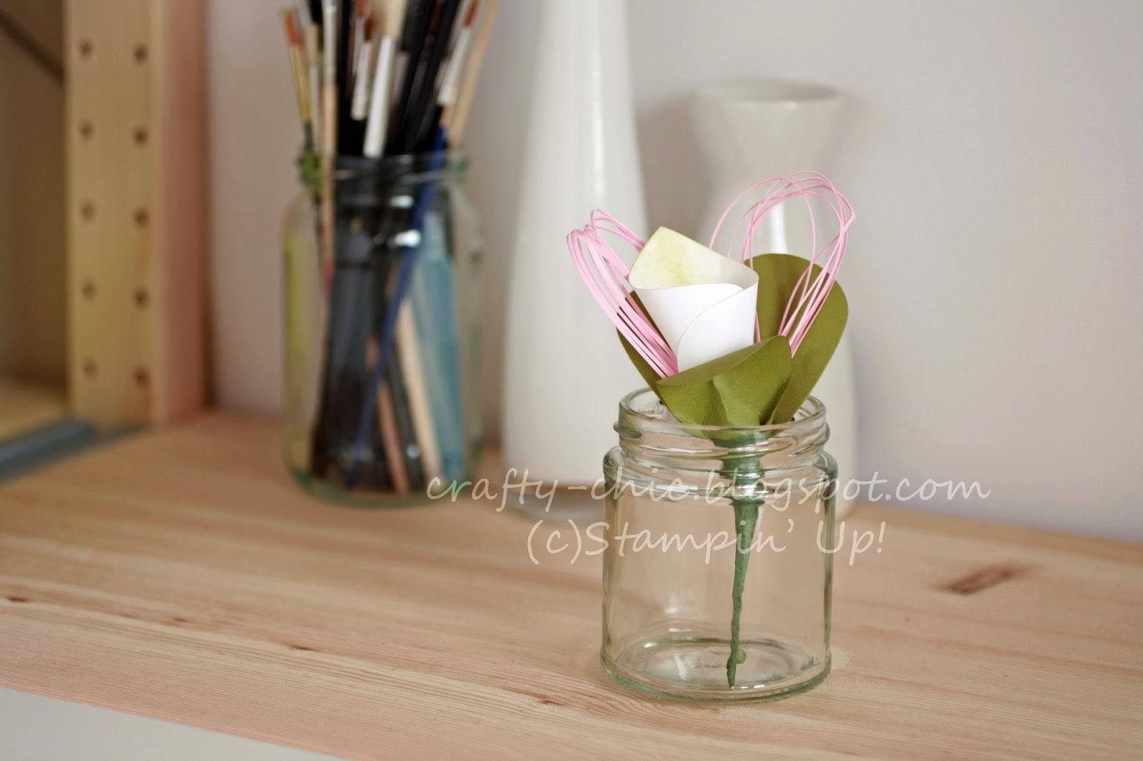 A picture of a paper lily in a glass jar