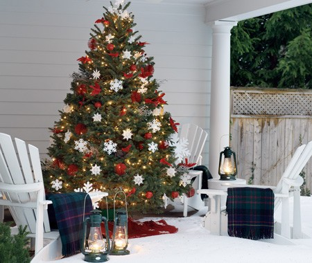 a muskoka outdoor christmas tree decorated with white snowflakes red balls and red birds the christmas tree is surrounded by white muskoka chairs - Outdoor Christmas Tree Decorations For Birds
