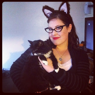 Me, wearing cats-eye glasses, cats ears, a cat tag on a necklace and with eyeliner-whiskers, holding a black cat with a white chest. I am wearing a black dress with a white cami - the same markings as the cat.