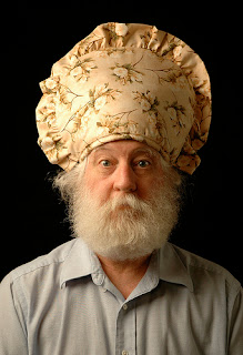 serious looking white bearded man with a yellow flowered tea cosy on his head