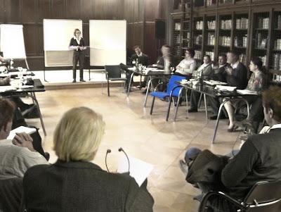 Ein dunkel getäfelter Tagungsraum mit Seminarteilnehmern und Vortragender. Aus dem in Naturtönen gehalten Bild sticht ein hellblauer Stuhl hervor.
