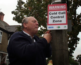 Alan Plant putting up a 'Cold Call Control Zone' sign
