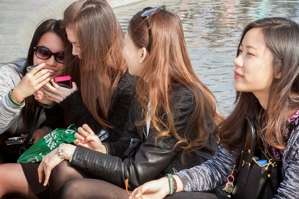 four Asian girls with a cell phone
