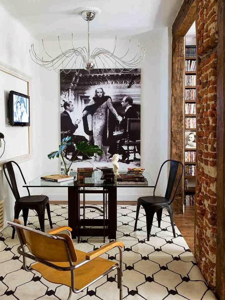 Aranżacja jadalni plakat na ścianie, czarne metalowe krzesła, czarno-biały dywan we wzory geometryczne