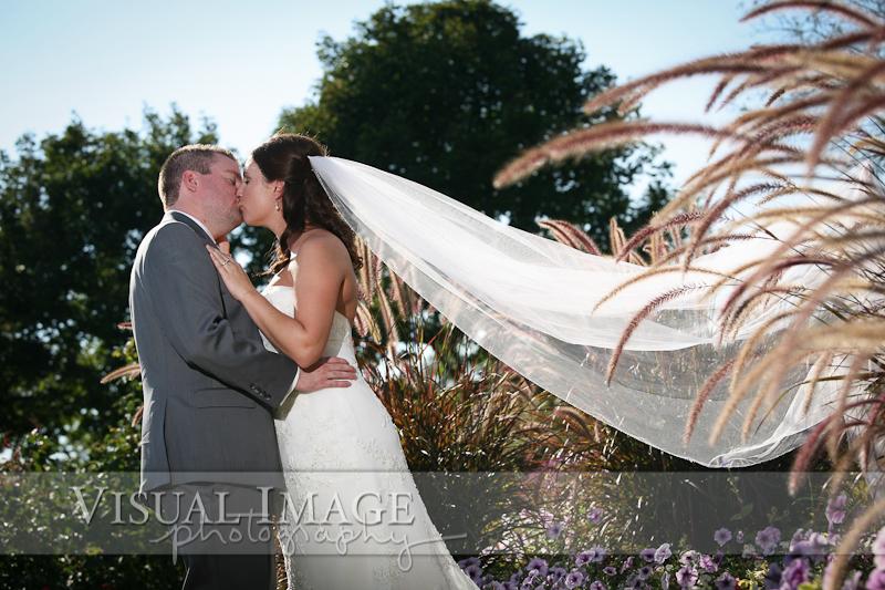 Groom kissing bride with long sunlit veil in Frame Park
