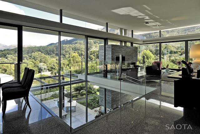 Picture of large interior area with living room and glass walls overlooking the hills