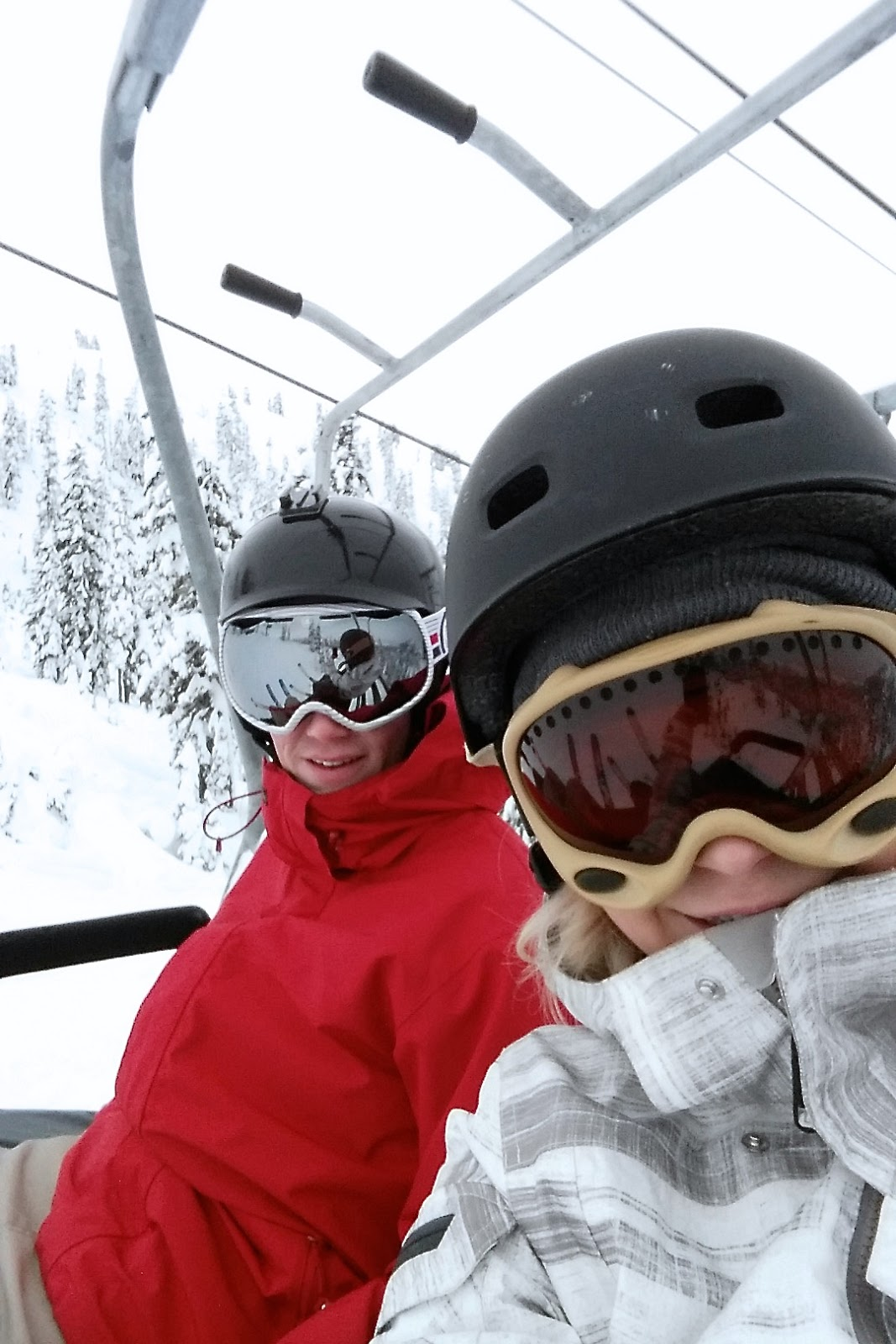 two skiers take a selfie on the chair lift