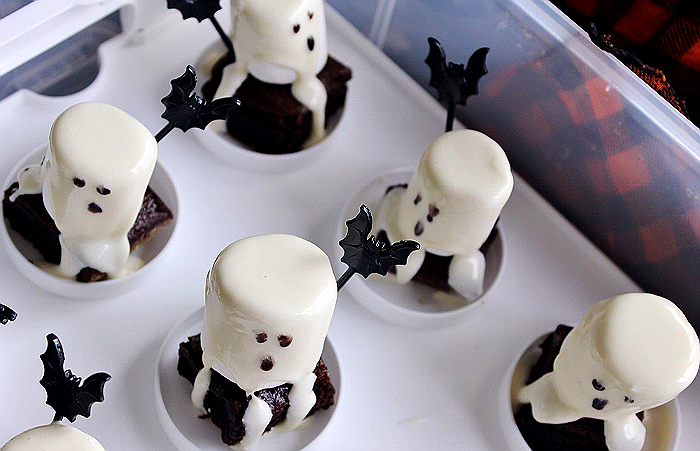 """Simple Brownie Ghosts- Simple Directions: Start with brownies- I do not care how you get brownies, I won't tell if you slaved over them for hours or not. Cut them into squares about 2"""" in width. Place 1 Jumbo Marshmallow atop each brownie square. Place the pre-made frosting of your choice into a microwave safe bowl and heat on high at 5 second increments until it can be stirred into an even liquid format. Spoon melted frosting over your mallows, allowing it to drip down the side like flowy ghost 'sheets.' Squirt some black food color or decorating gel on a plate and daub the end of a chopstick/skewer/cake pop rod (etc) into the black and daub tiny faces on your ghosts. Refrigerate until serving and enjoy!"""