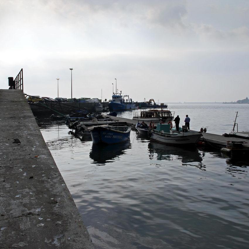Fotografia do cais em contra-luz. Alguns barcos ancorados.
