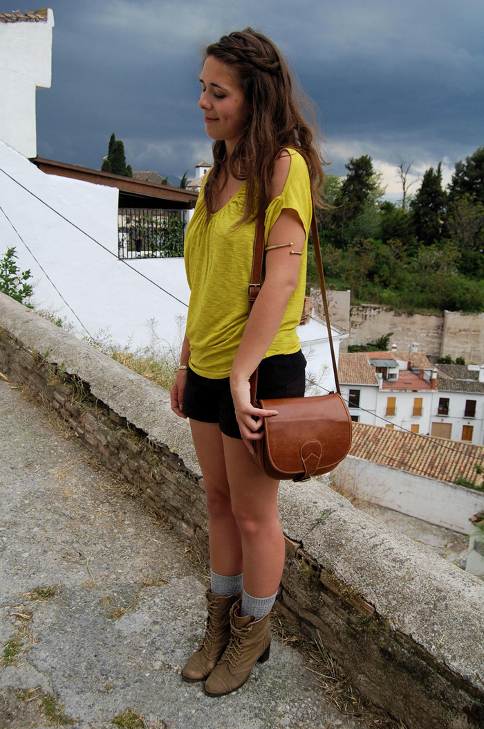 Chartreuse bouse worn with black shorts, gold armband, leather bag and combat boots.