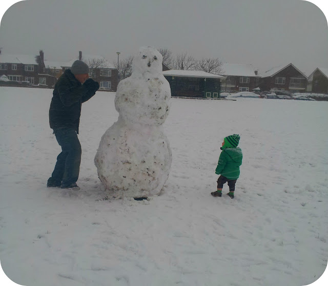 giant snowman, playing with snowman, father and son in snow