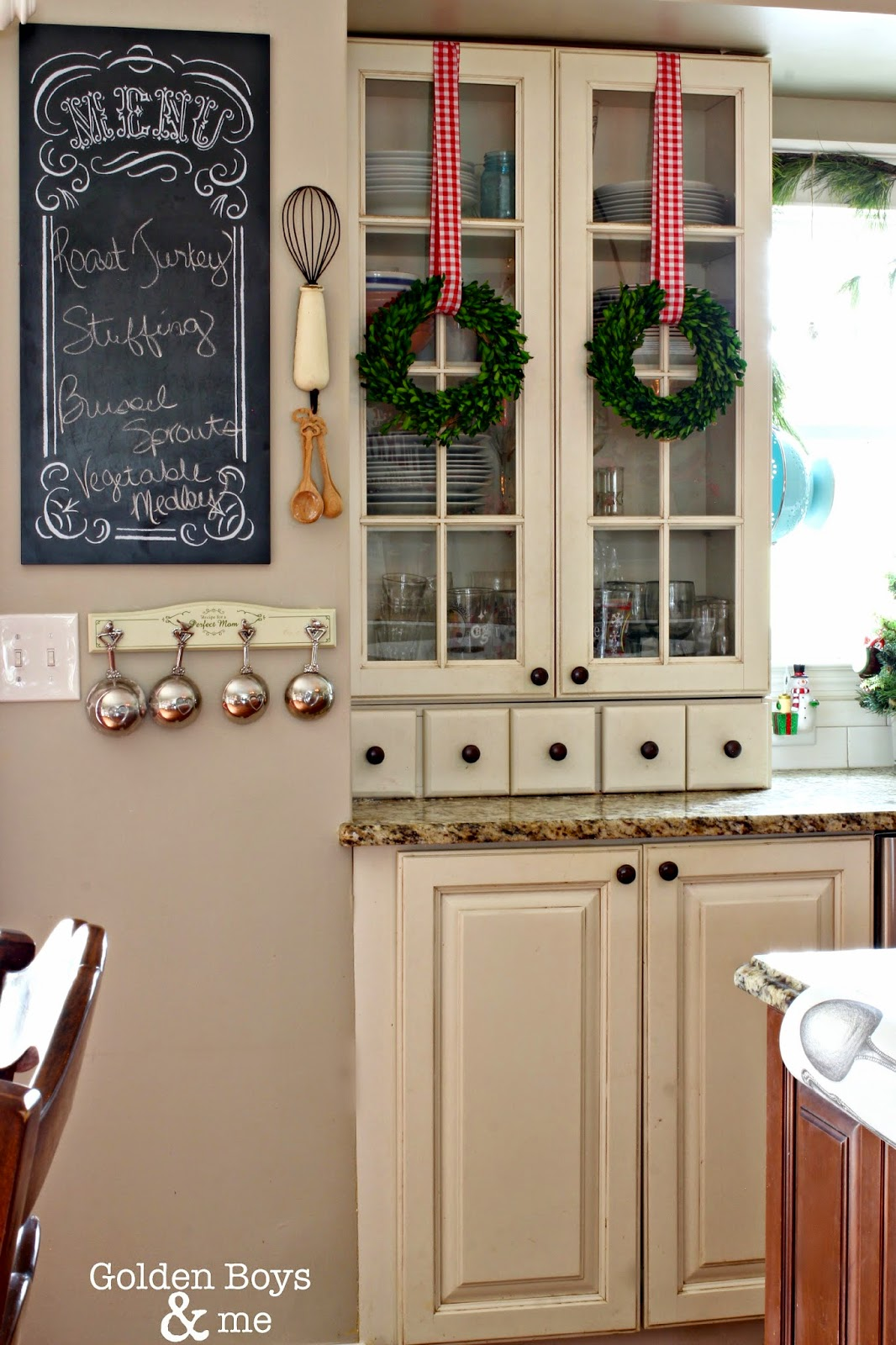 Preserved boxwood wreaths hung on glass cabinet doors in Christmas kitchen.-www.goldenboysandme.com