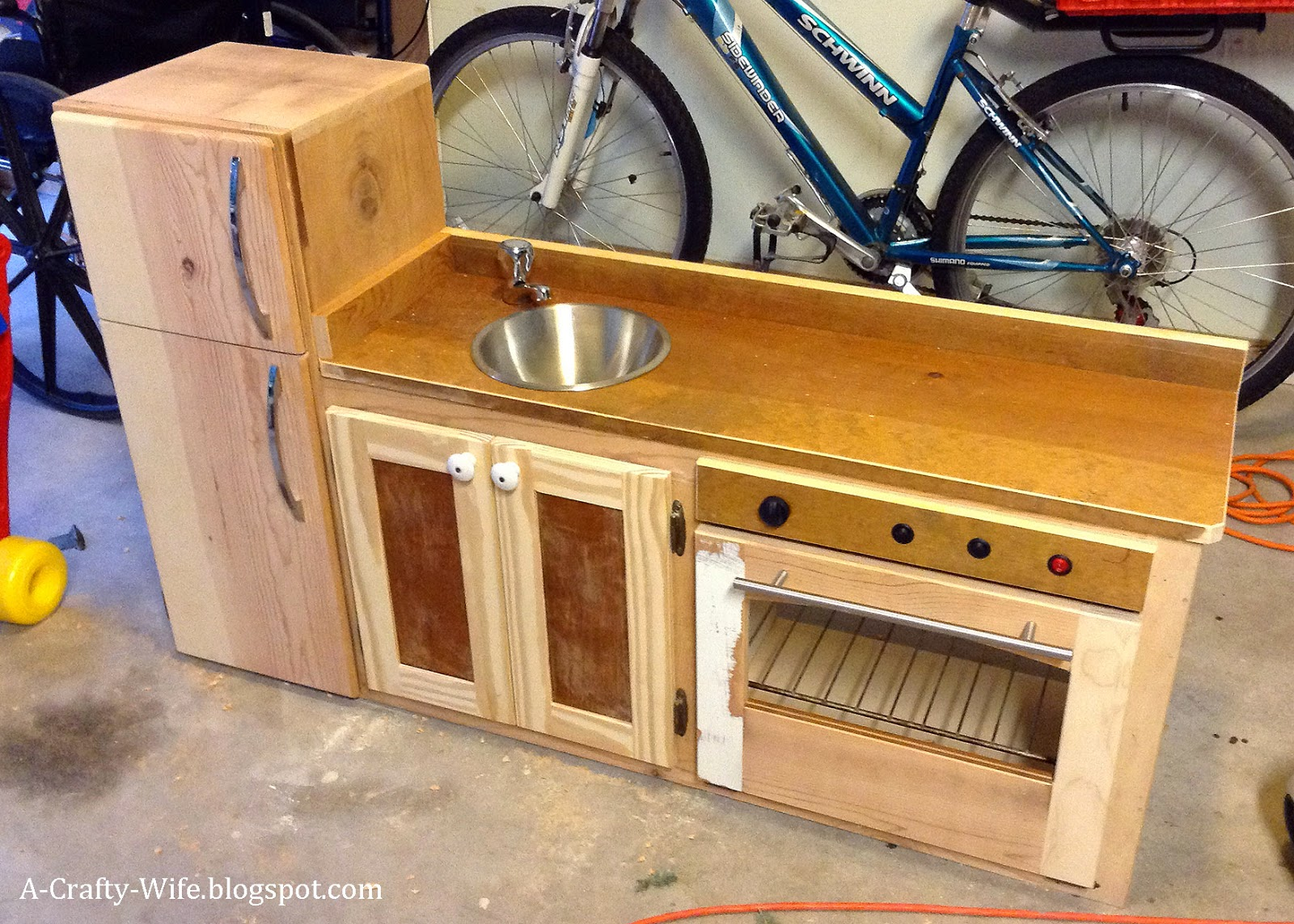 Make play kitchen from old kitchen cabinets and scrap wood.