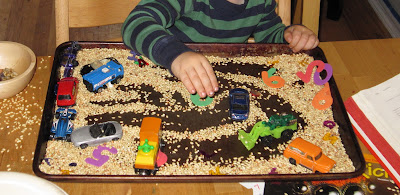 Sensory rice tray with toy cars and trucks
