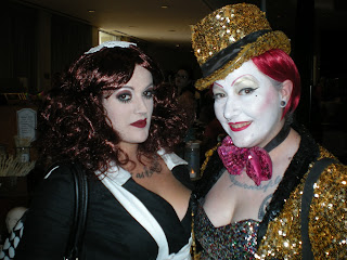 Two costumed con attendees: Magenta the maid with glitter dressed Columbia from The Rocky Horror Picture Show.