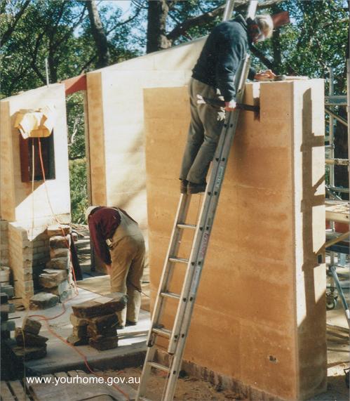 Casa en construcción con muros de tierra cruda apisonada