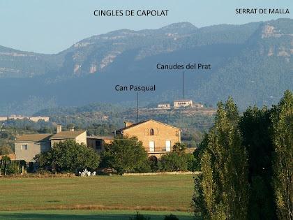 La masia de Can Pasqual amb els Cingles de Capolat al seu darrere, des dels camps de La Cabana