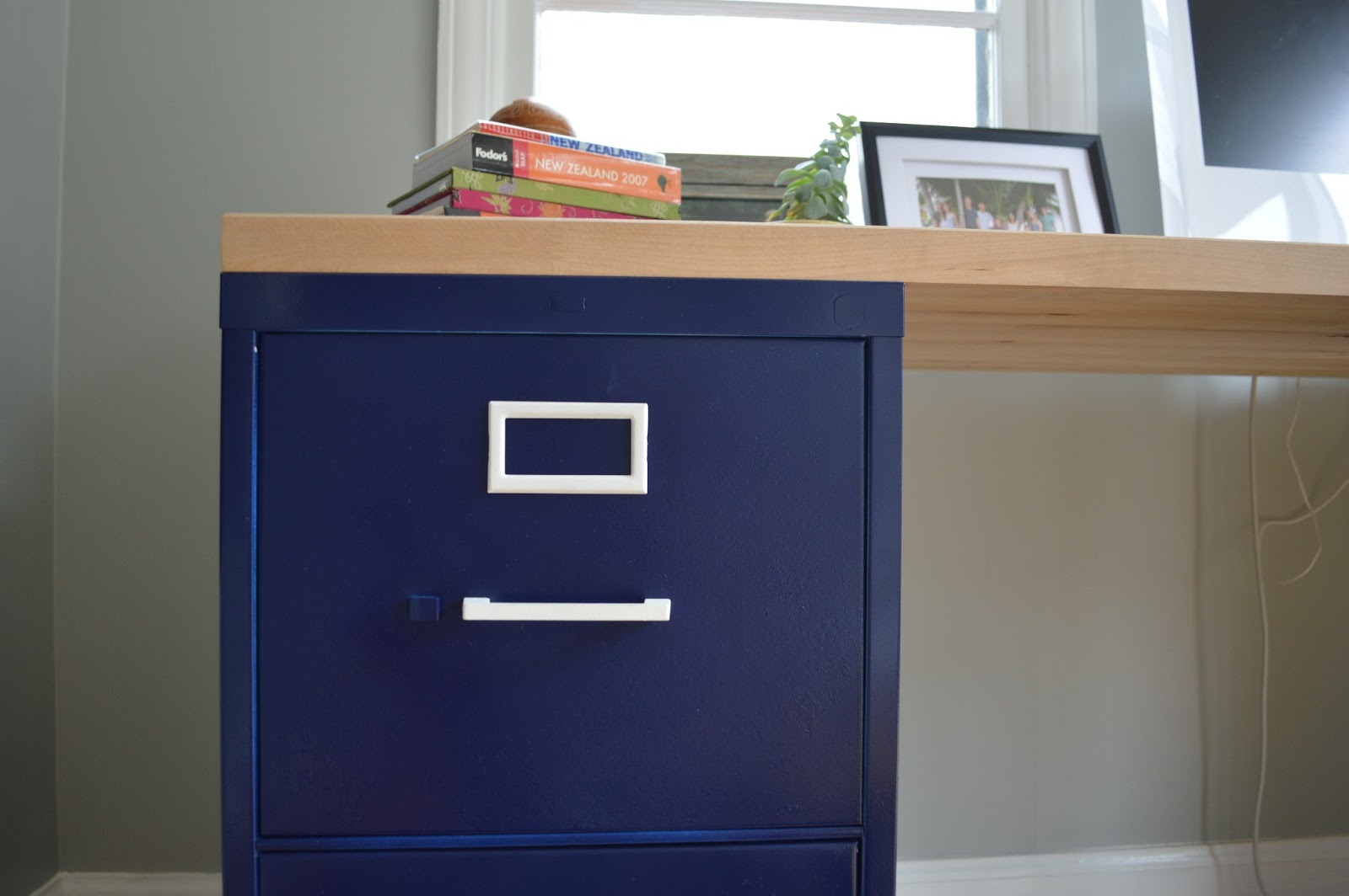 Two Bruised Filing Cabinets... Black And The Other Beige... Are Turned Navy  Blue With White Accents, Using Paint From A Can.