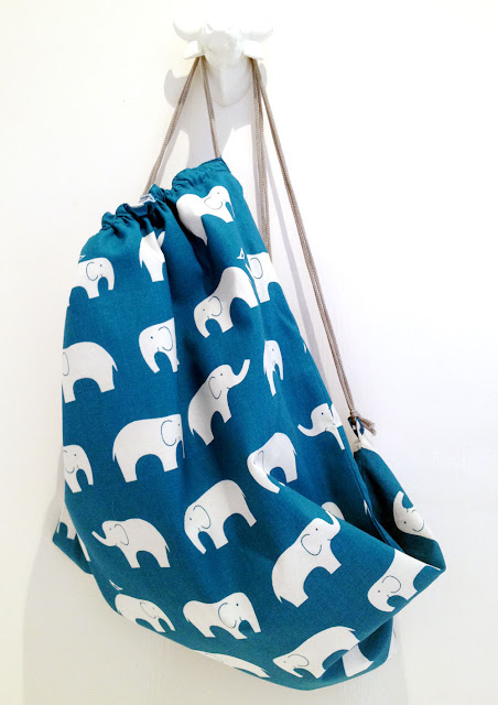 teal bag, white elephants hanging from buffalo peg