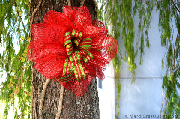 Deco mesh Christmas bow decorates a tree