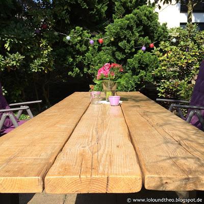 Gartentisch mit Blumenvase, Windlichtern und Häkeldeckchen