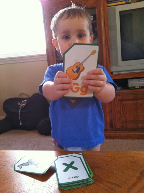 Two year old playing with alphabet flash cards.