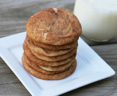 snickerdoodles stacked on white plate with a glass of milk in the background