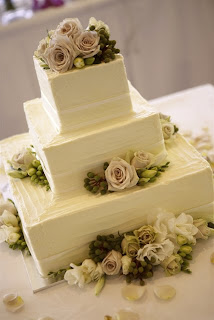 A traditional wedding cake with square tiers and interesting texture.