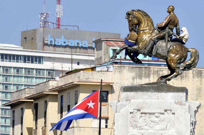 Trabajadores de la Empresa Constructora Puerto Carenas de la Oficina del Historiador de la Ciudad realizan labores de pulido de la escultura del Mayor General del Ejercito Libertador Antonio Maceo, en el parque que lleva su nombre, en La Habana, Cuba, el 24 de julio de 2013.