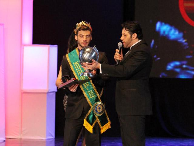 Momento em que Ralph Santos, Mister Universo Brasil 2011 e atual coordenador do concurso, entrega o troféu para Lucas Kubistchek. Foto: Orlando Oliveira/Ag. Brayan Celebrity/Divulgação